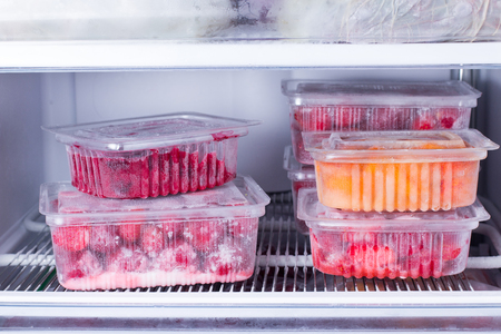 Frozen fruits and berries in a container in the freezer. Frozen food