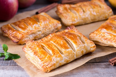 Puff pastry filled with apples on a wooden table