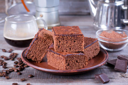 Homemade brownies in plate on rustic wooden table