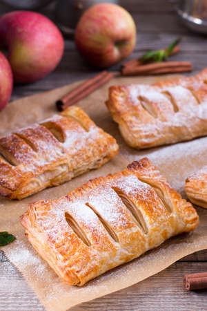Puff pastry with apples and powdered sugar on a wooden table