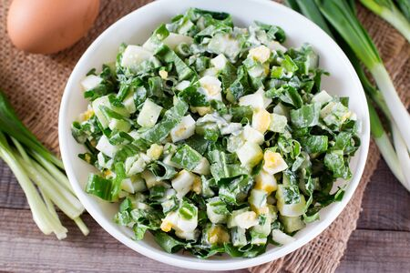Fresh summer light salad with eggs and greens on a table