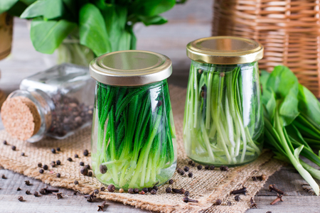 Pickled garlic sprouts in a glass on a wooden table. Home canning Banque d'images