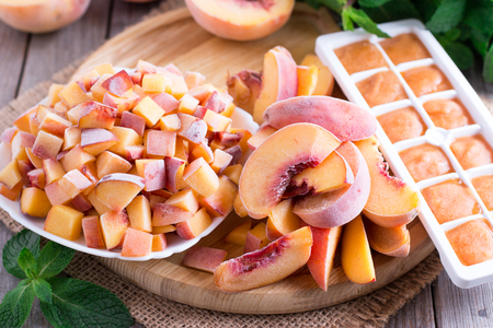 Frozen peaches on a wooden board (slices, slices, puree) Stock fotó