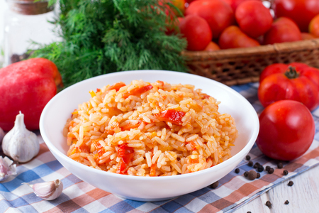 Bowl full of rice with tomatoes on white wooden background