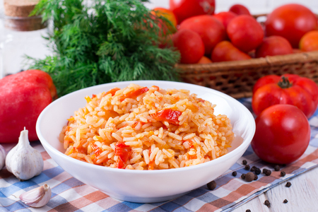 Spanish brown rice with tomatoes on white wooden background