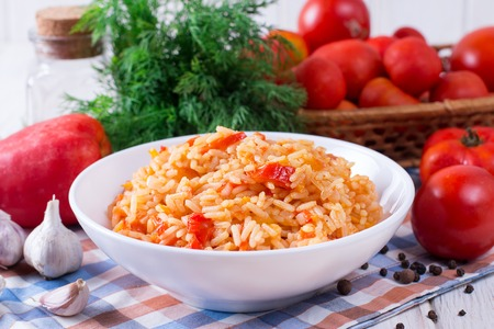 Mexican Rice - Rice cooked with tomato sauce in a white bowl Stock Photo