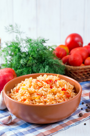 Rice with tomatoes and sweet pepper on wooden background