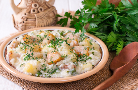 Millet porridge with bacon in a dish on the table. Russian kitchen Stockfoto