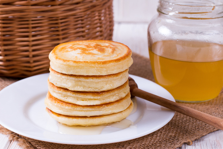 Stack of pancakes with honey in plate on white table, delicious dessert for breakfast.