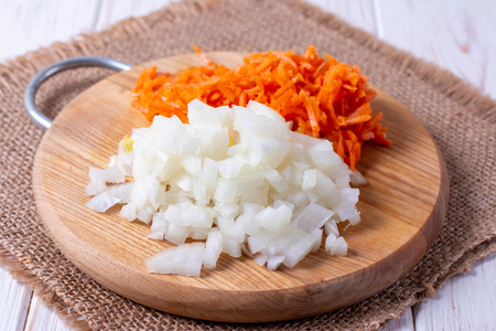Onions and carrots chopped on a cutting board on a wooden table, horizontal 写真素材