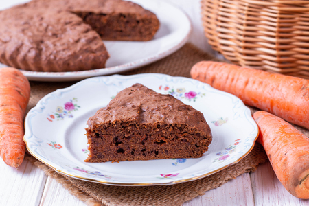 Chocolate cake with carrots in a bowl on a white wooden table