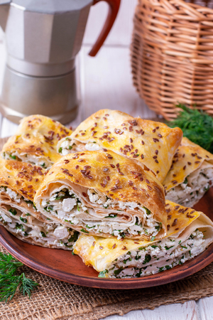 Lavash roll with cottage cheese and greens on a plate. Cold appetizer