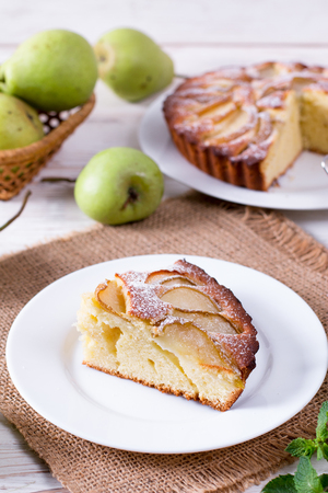 Piece of a pear cake on a white plate on a white table with pears in the background Standard-Bild