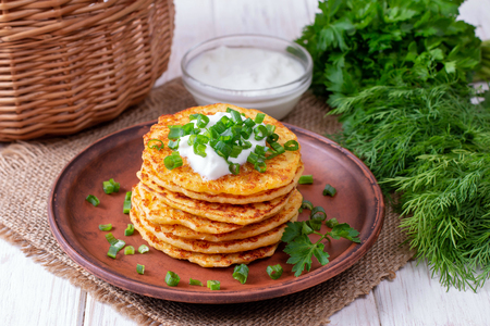 Pancakes with cheese with sour cream and green onions in a plate Фото со стока