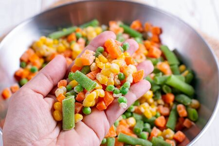 Homemade frozen vegetables in a metal bowl. Healthy food storage concept. Banco de Imagens