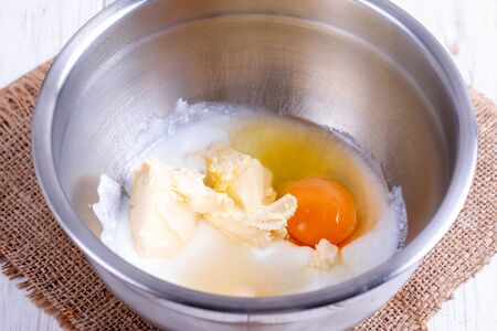 Mixing butter, sugar and eggs in bowl with mixing machine, making pie