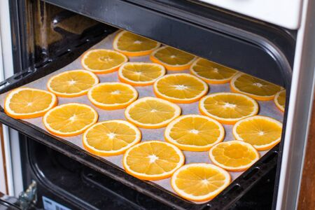 Sliced fresh orange on a baking tray in the oven