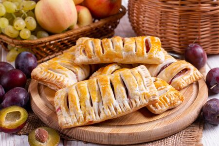 Puff pastry with plums for dessert on a wooden table