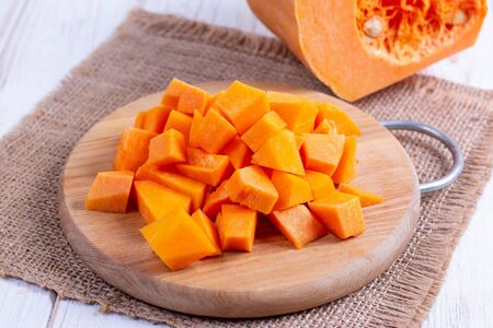 Cubes of pumpkin on cutting board on wooden table Stockfoto