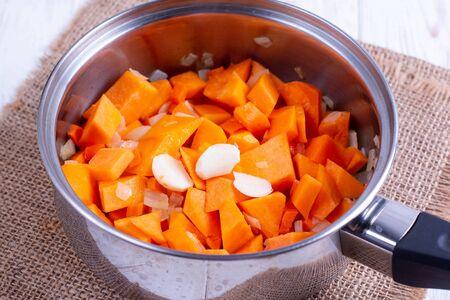 Pumpkin, carrots and garlic in a pan. Cooking Pumpkin Soup
