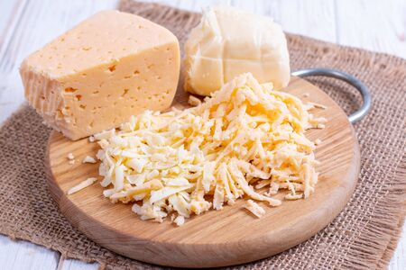 Grated cheese on a wooden cutting board closeup Stockfoto