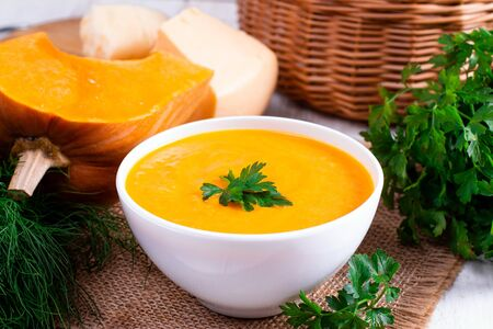 Pumpkin puree with cheese in a white bowl on wooden background