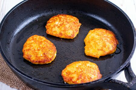 Pumpkin pancakes with honey in a pan. Cooking