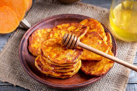 Pumpkin pancakes with honey on a plate on a wooden background Stockfoto