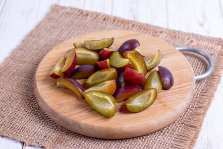 Sliced plums on a cutting board on a wooden table Stockfoto