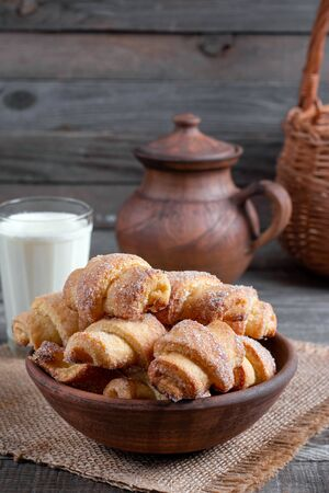 Tasty baked rolled or bagels cookies with sugar on rustic wooden table