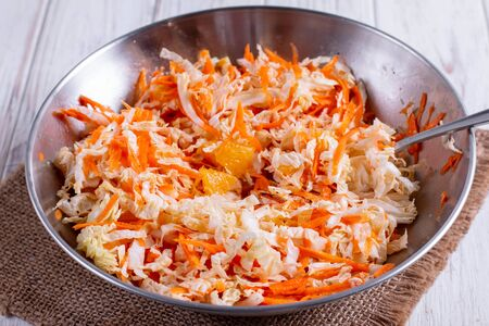 Sliced carrots of cabbage and oranges, carrots. Fresh cabbage salad with oranges and carrots