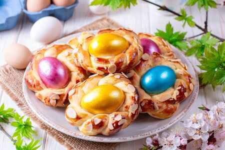 Homemade sweet Italian Easter Bread Rings with dyed eggs on an old white wooden table, view from above, close-up Stock Photo