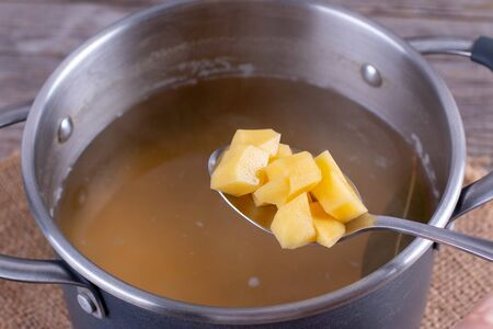 Cooking soup. Chopped potatoes in soup. Food background