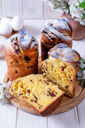 Traditional easter cake craffin (kraffin) with powdered sugar on the table. Easter cakes and decorative flowers. Foto de archivo - 137684225