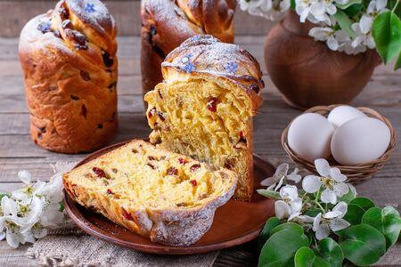 Traditional easter cake craffin (kraffin) with powdered sugar on the table. Easter cakes and decorative flowers. Foto de archivo - 137684785