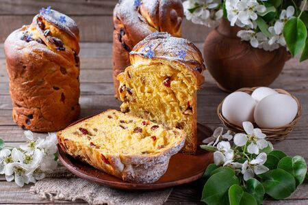 Traditional easter cake craffin (kraffin) with powdered sugar on the table. Easter cakes and decorative flowers. Foto de archivo - 137684864