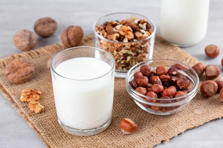 Vegan milk from nuts in glass jar with various nuts on white wooden background