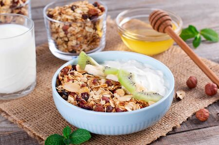 Granola with Greek yogurt kiwi and banana in a bowl with a spoon. Fitness diet for weight loss, proper and tasty food