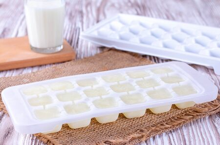 Ice cube tray with frozen milk on a white wooden table, closeup
