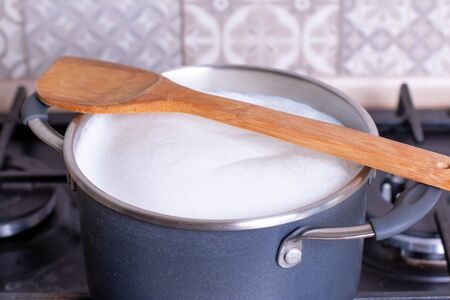 Boiling milk in a pan, wood spoon on the top, closeup