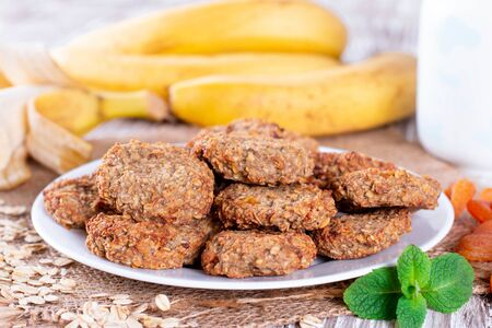 Homemade oatmeal cookies with banana and dried fruits on wooden table, close up