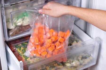 Bags with frozen vegetables in refrigerator. Frozen pumpkin cubes, closeup Banque d'images