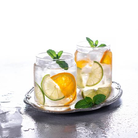 Orange cocktail with mint and lime. Cold refreshing drink or beverage with ice. Cold drinks with ice and mint.
