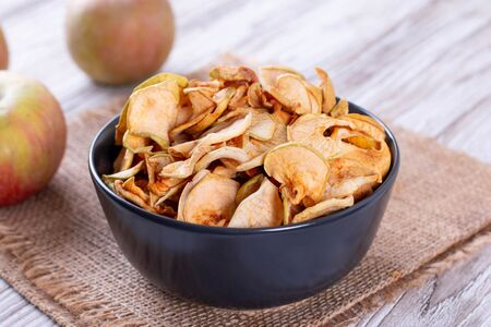 Dried apples in a bowl with apples on the table