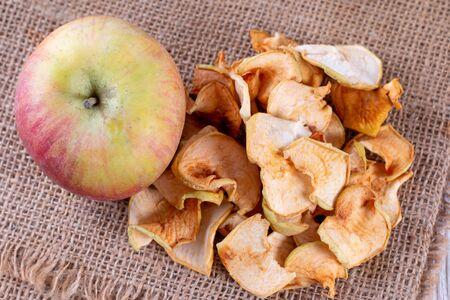 Homemade dried organic apple sliced on wood background