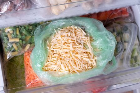 Frozen grated cheese. Frozen food in the freezer