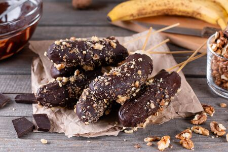 Frozen banana covered with chocolate and nuts on wooden rustic table Zdjęcie Seryjne
