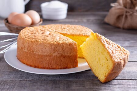 Homemade round sponge cake or chiffon cake on white plate so soft and delicious with ingredients: eggs, flour, milk on wood table. Homemade bakery concept for background and wallpaper.