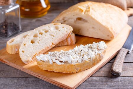 Freshly baked sliced bread on wood cutting board with cottage cheese, ciabatta