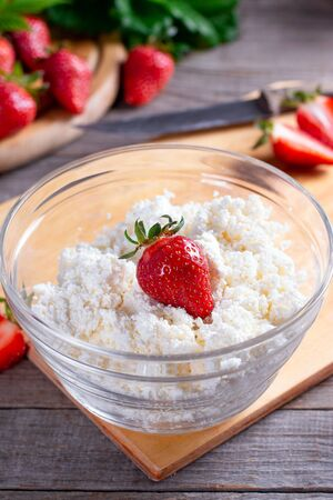 Organic cottage cheese with strawberries in a glass bowl. Delicious breakfast.